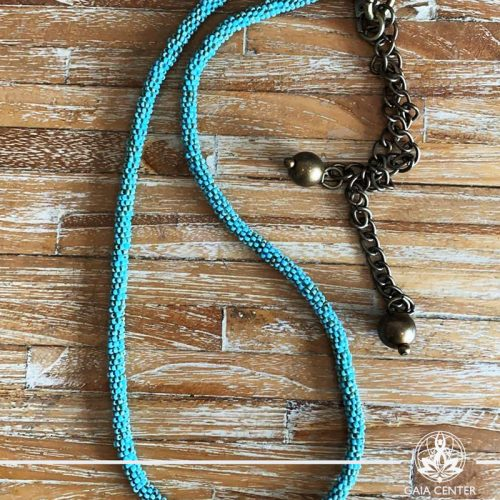 Summer necklace - blue or turquoise color beads on a long string with metal balls charms. Summer essential jewellery at Gaia Center in Cyprus. Shop online at https://gaia-center.com. Cyprus and Worldwide shipping.