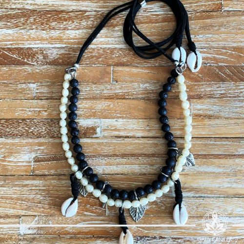 Summer necklace - black lava stone with white pearls imitation with sea shells charms on a string. Summer essential jewellery at Gaia Center in Cyprus. Shop online at https://gaia-center.com. Cyprus and Worldwide shipping.