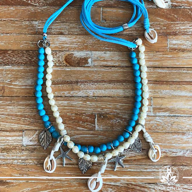 Summer necklace - turquoise and white pearls imitation design with sea shells charms on a string. Summer essential jewellery at Gaia Center in Cyprus. Shop online at https://gaia-center.com. Cyprus and Worldwide shipping.