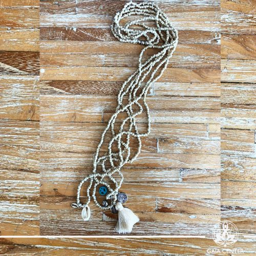 Summer necklace - cream color beads sea shell and decor charms. Summer essential jewellery at Gaia Center in Cyprus. Shop online at https://gaia-center.com. Cyprus and Worldwide shipping.