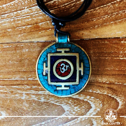 Tibetan Pendant Om symbol and yantra or mandala design. Red coral, lapis lazuli and turquoise. Adjustable black string. Selection of Tibetan Jewelry made of crystals, gemstones, combination of metals at Gaia Center | Cyprus.