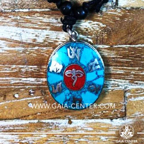 Tibetan Pendant turquoise and red color. Made from metal with engraved buddhist design, buddha eyes on an adjustable black string. Tibet Selection of Tibetan Jewelry made from crystals, gemstones, combination of metals at Gaia Center   Cyprus.
