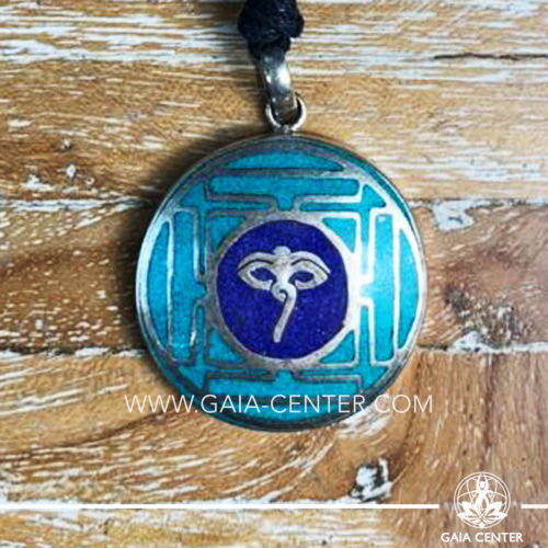Tibetan Pendant with Buddha wisdom eyes symbol. Metal inlaid with semiprecious gemstones. Adjustable black string. Selection of Tibetan Jewelry made from crystals, gemstones, combination of metals at Gaia Center | Cyprus.