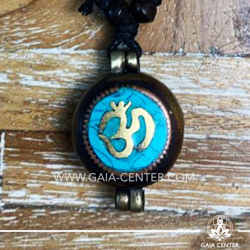 Tibetan Pendant Gau box amulet with Om symbol. Metal inlaid with semiprecious gemstones. Adjustable black string. Selection of Tibetan Jewelry made from crystals, gemstones, combination of metals at Gaia Center | Cyprus.